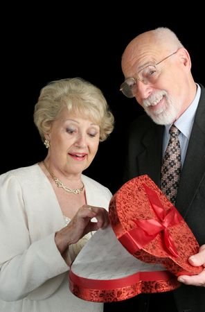A senior man very proud of himself for surprising his wife with Valentine candy.  Black background. photo
