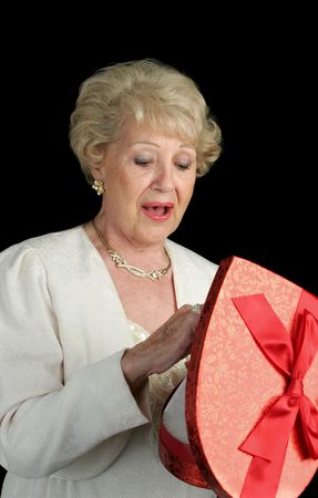 A beautiful senior woman choosing a chocolate from a box of Valentines candy.  Black background photo