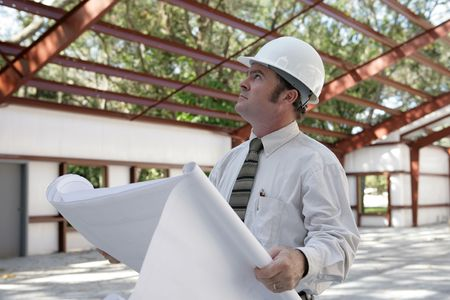 A construction inspector holding blueprints and looking at the roof beams of a steel building in progress. photo