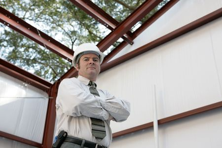 A construction inspector standing inside an unfinished steel frame building. ` photo