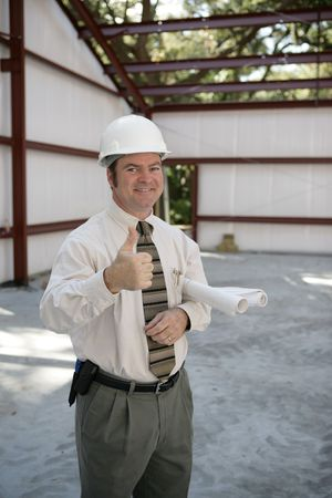 A satisfied construction inspector holding blueprints and giving a thumbsup.