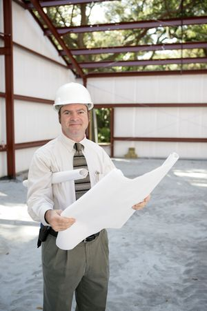 A construction inspector on the job site holding blueprints and smiling. photo