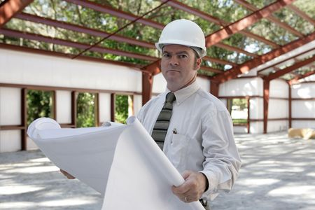 A construction engineer reviewing blueprints on the jobsite. photo