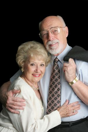 An attractive, affectionate senior couple on a black background. photo