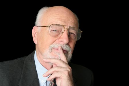 An intelligent senior man with a thoughtful expression over a black background.