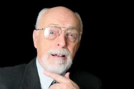 distinguished: A handsome, distinguished looking senior man on a black background looking surprised. Stock Photo