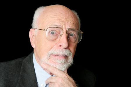 distinguished: A distinguished senior man with a scared expression over a black background.