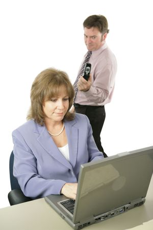 A woman working, unaware that a male coworker is photographing over her shoulder with his camera phone.  Isolated on white.