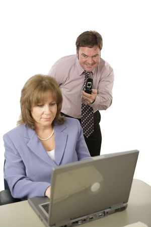 A man with a camera phone taking pictures of a coworkers computer screen behind her back.  Isolated on white with focus on man.