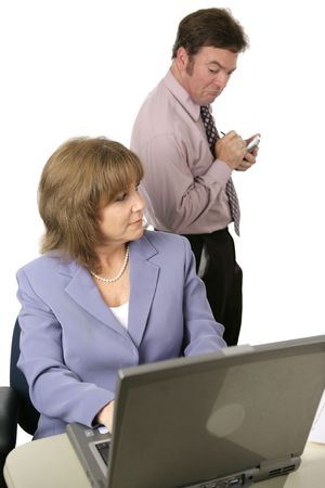 A male coworker spying over a female coworkers shoulder and taking notes on what he sees.  Isolated on white.  Focus on female.
