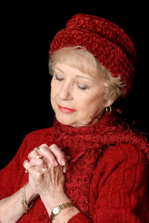 A beautiful senior lady in red with her hands folded in prayer.  Black background. photo
