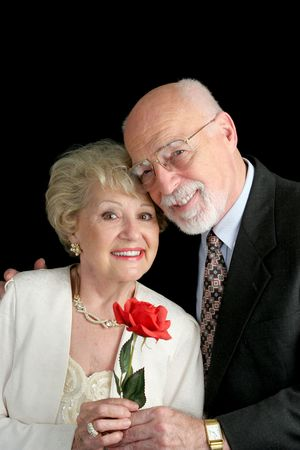 A handsome, romantic, senior couple holding a red rose, posing against a black background. photo