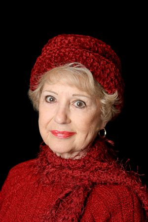 A beautiful senior lady in red sweater and hat.  Black background. photo