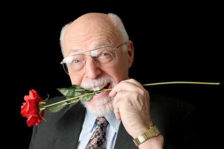 A handsome senior man with a red rose in his teeth.  Isolated on black.