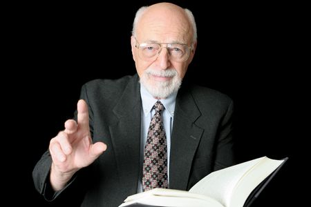 preaching: A handsome older man either teaching or preaching from a book.  Isolated on black.