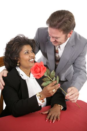 An attractive interracial couple on a date.  He surprises her with a red rose. Stock Photo - 700152