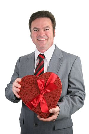 A handsome man in a suit holding a box of valentines chocolates.  Isolated on white. photo