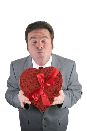 A man in a suit holding a red valentines heart and puckering up for a kiss.  Isolated on white.