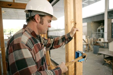 licensed: An electrician on a construction site hammering a switch box into a wood beam.  Model is a licensed master electrician. Work being performed to code.