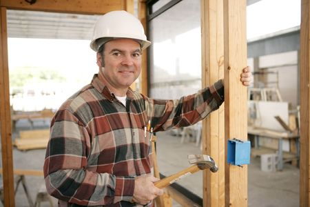 An electrician on a construction site installing an electrical box. Model is a licensed master electrician. Work depicted is accurate and in compliance with codes and safety standards.