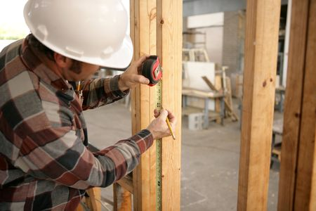 A construction electrician measuring up 48 inches to install a switch box. Model is a licensed master electrician.  All work being performed in compliance with code and safety regulations. Stock Photo