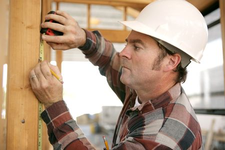 A construction working taking measurments and marking a wood beam on a house frame. photo
