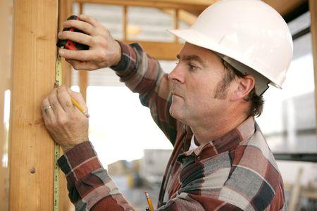 carpintero: Una construcci�n que trabaja tomando measurments y marcando una viga de madera en un marco de la casa.