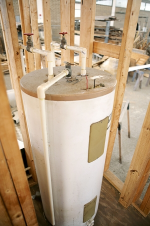 Construction site with hot water heater installed.  Focus on center top of water heater. photo