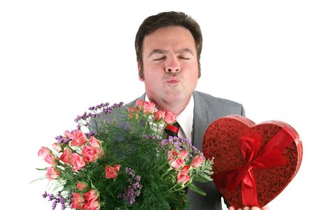 A man holding Valentines candy and flowers and puckering up for his thank you kiss.  Isolated on white. photo