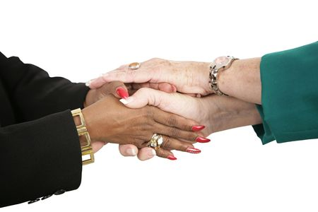 The hands of two female business people holding hands.  Isolated on white.