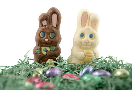 Milk chocolate and white chocolate Easter bunnies in love, running through a field of easter grass and chocolate eggs.  Shallow depth of field. photo