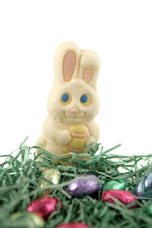 A white chocolate easter bunny in a nest with foil wrapped chocolate eggs.  White background. Stock Photo