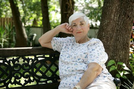 A sweet senior lady relaxing on a park bench.