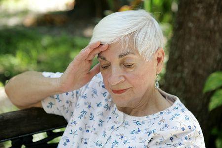 sad old woman: Una mujer mayor que da masajes a sus templos. Ella es triste yo sufridora de un dolor de cabeza. Foto de archivo
