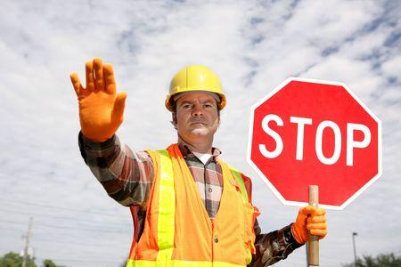 se�ales trafico: Un trabajador de la construcci�n detener el tr�fico, la celebraci�n de una se�al de stop.  Foto de archivo