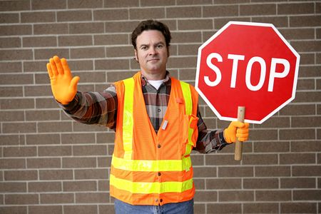 A friendly school crossing guard holding a stop sign. photo