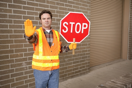 A school crossing guard holding a stop sign.  Room for text. photo