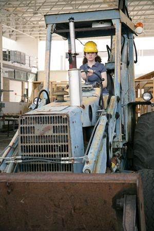 A female construction worker driving an earth mover on a construction site. photo