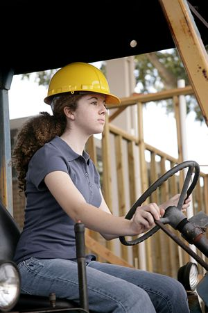 A female construction worker driving heavy equipment.  Vertical view.