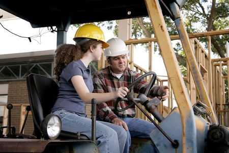 building safety: A construction foreman instructing a new worker on driving heavy equipment. Focus on the foreman.