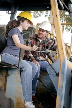 heavy industry: A construction foreman teaching a young worker how to drive heavy equipment.