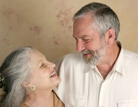 midlife: A mature couple laughing together.  Focus on her.
