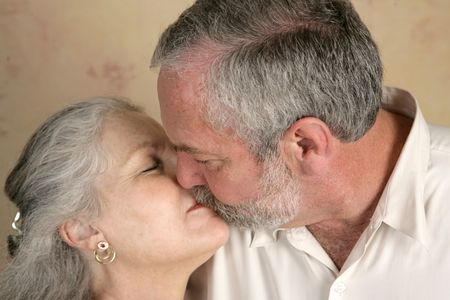 A mature couple sharing a passionate kiss.  Focus on him.   photo