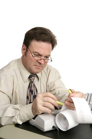 A man going over his accounts using a highlighter to identify issues.  Isolated on white.
