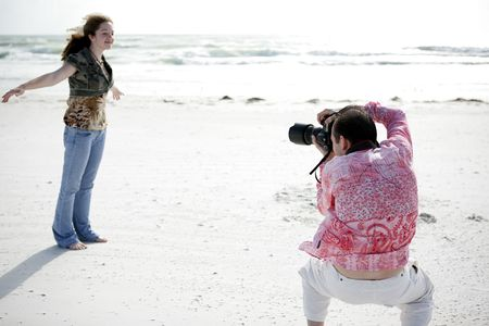 A photographer working with a model to get the right pose. Shallow depth of field with focus on photographers head. photo