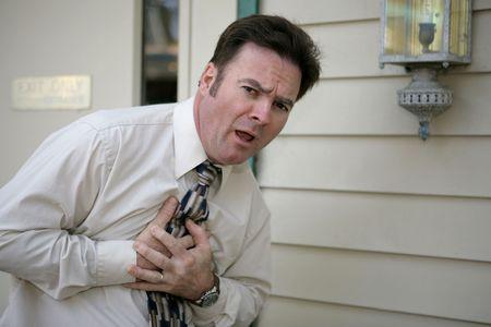 angina: Ein mittlerer gealterter Mann, der Schmerzen in der Brust hat und Sie nach Hilfe betrachtet.