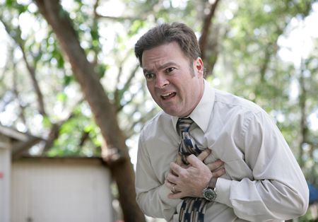 A forty year old businessman outdoors experiencing chest pain.