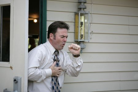 coughing: A middle aged man leaving a building and having a coughing fit.