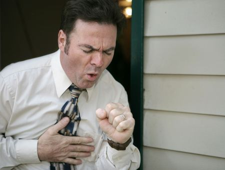 coughing: A man leaving work early because of a coughing fit. Stock Photo
