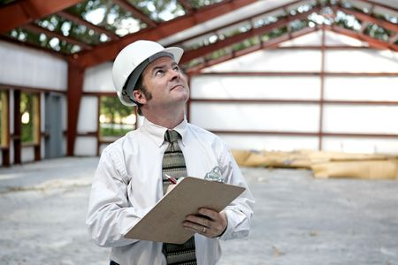 engineering clipboard: A building inspector examining the the steel girders in a building under construction.  Horizontal view.